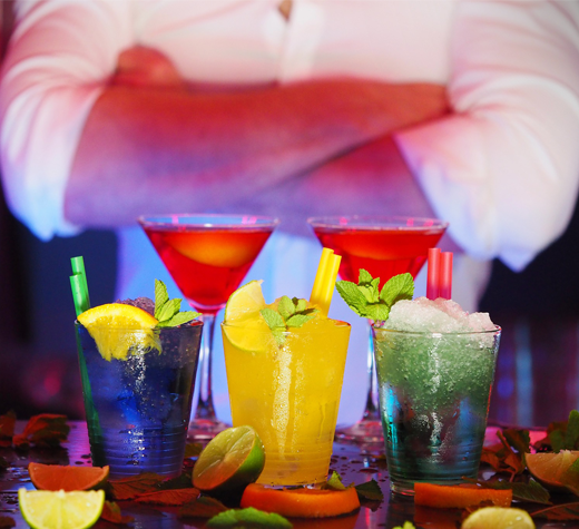 Flair bartender standing infront of drinks | Bartenders And More