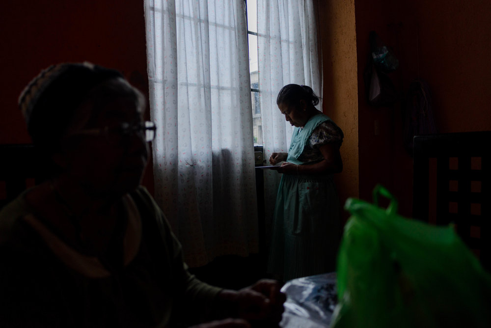 Agustina Marcos tells a story while her daughter and craftswoman Hermenegilda Ascenio Marcos looks at her food under the window light in the background.