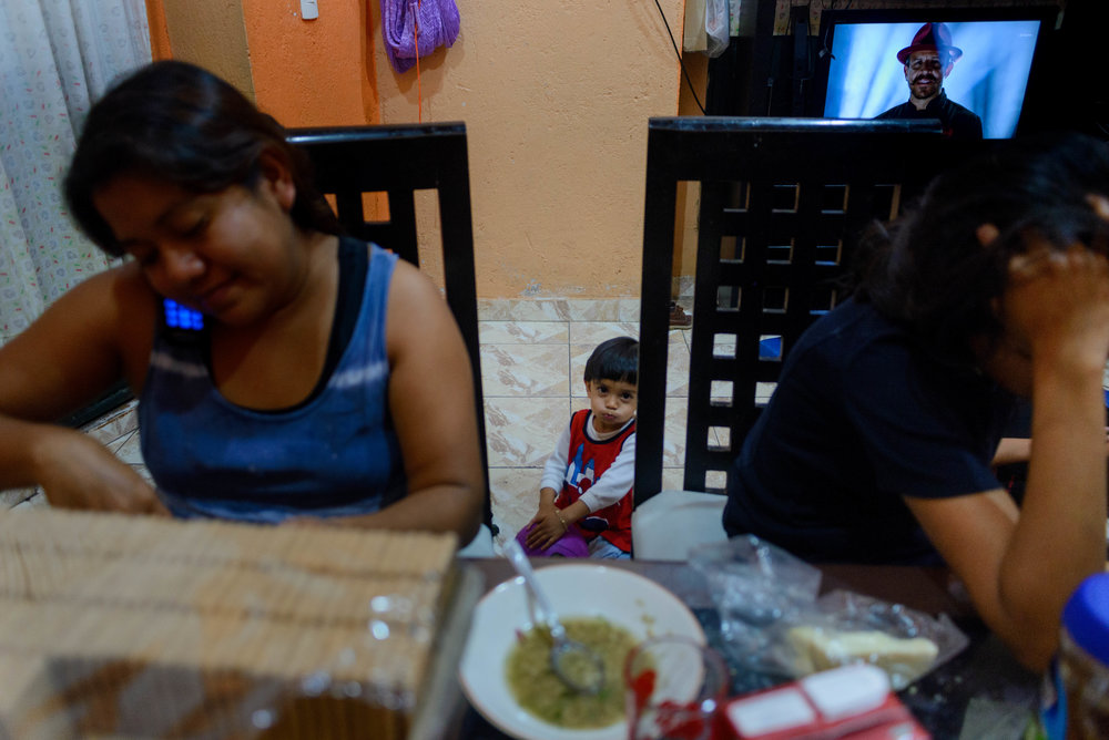 Jael looks at the camera while his mother speaks to his father on the phone one evening during dinner.