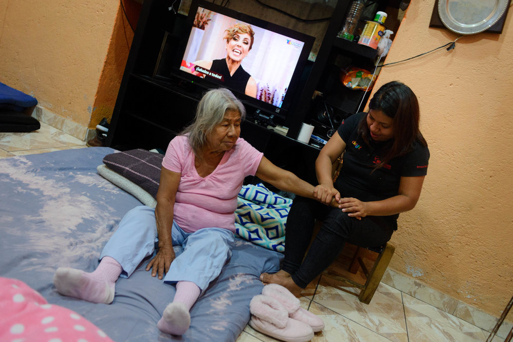 As grandmother Augustina prepares to sleep on a mattress in the living room, her granddaughter massages her arm.