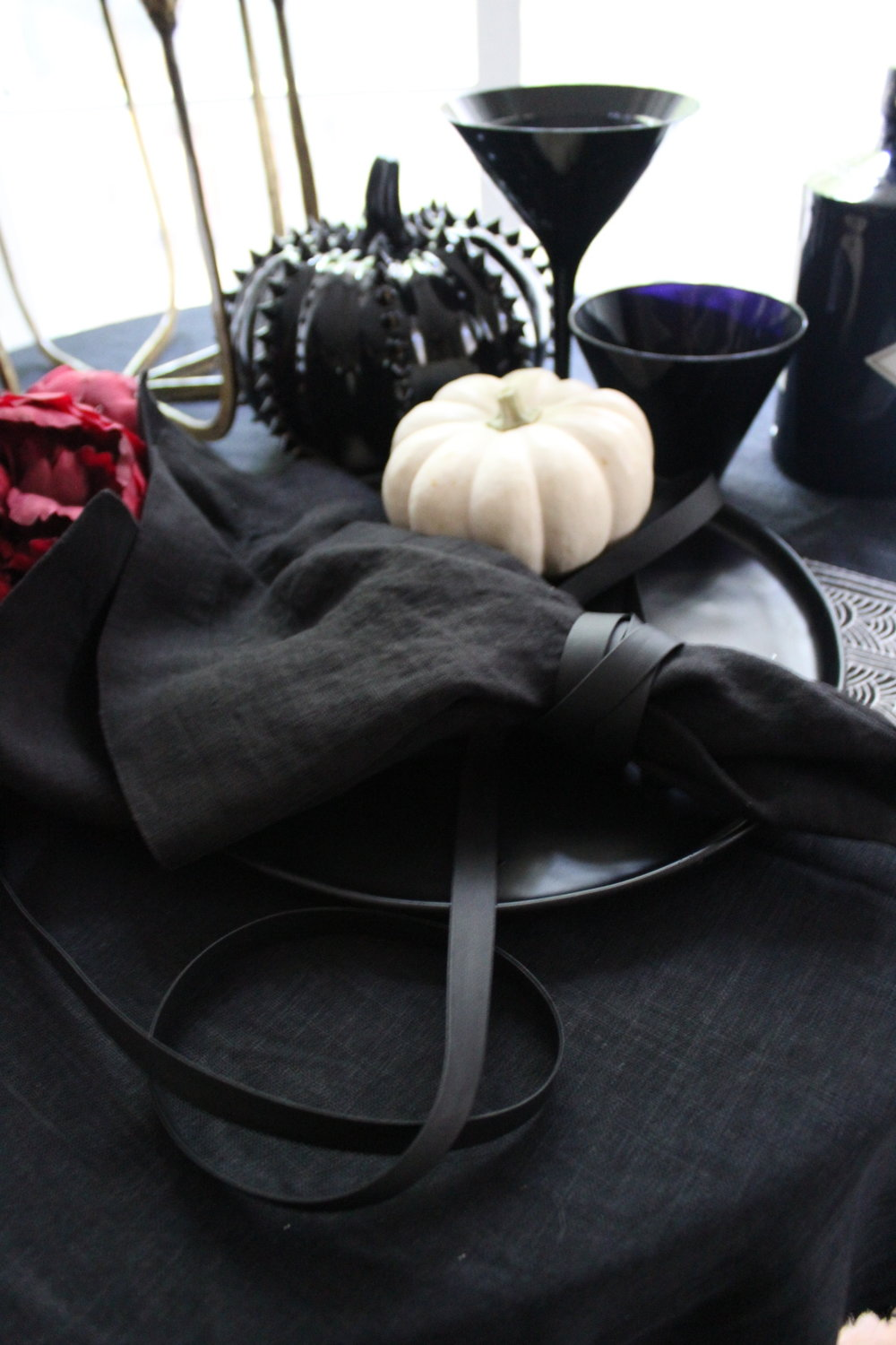 LEATHER...a few yards of faux leather ribbon from a local fabric store make excellent napkin rings. Leave a little excess to drape on the table for a moody effect.  LINEN...while you are at the fabric store, order a couple yards of black linen for a gauzy tablecloth. Save on ironing time and leave it bunching and the ends frayed. Splurge on linen napkins that you would use year round and save on the tablecloth that you will probably only use once a year.
