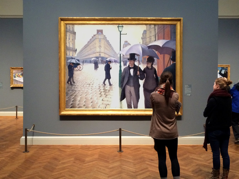 Gustave Caillebotte,  Paris Street; Rainy Day,  1877 exhibited at the Art Institute of Chicago. At 7′ 10″ x 6′ 1″ (239 x 185cm), the foreground figures are life-size and feels like you can just walk into the scene.