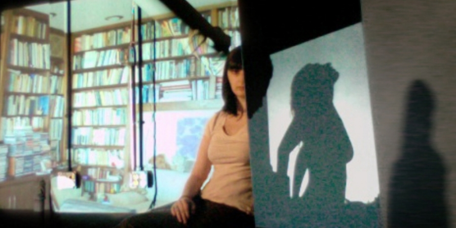 Actual  (no Photoshop)  Webcam feed of Projections and Mirror mockup. The bookshelves are a projected image. The central figure is real, split by a mirror reflecting the shadow of another figure.