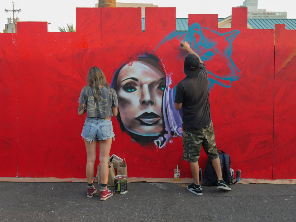 A pair of artists paint a temporary mural outside of Cobra Arcade Bar in Phoenix, Ariz. on Sept. 1, 2017.