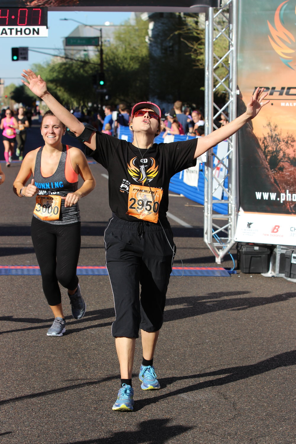Sandy Owen, 48, throws up her arms after crossing the finish line at the 42nd annual TV Phoenix 10K/Half Marathon in Phoenix, Ariz. on Nov. 5, 2017.
