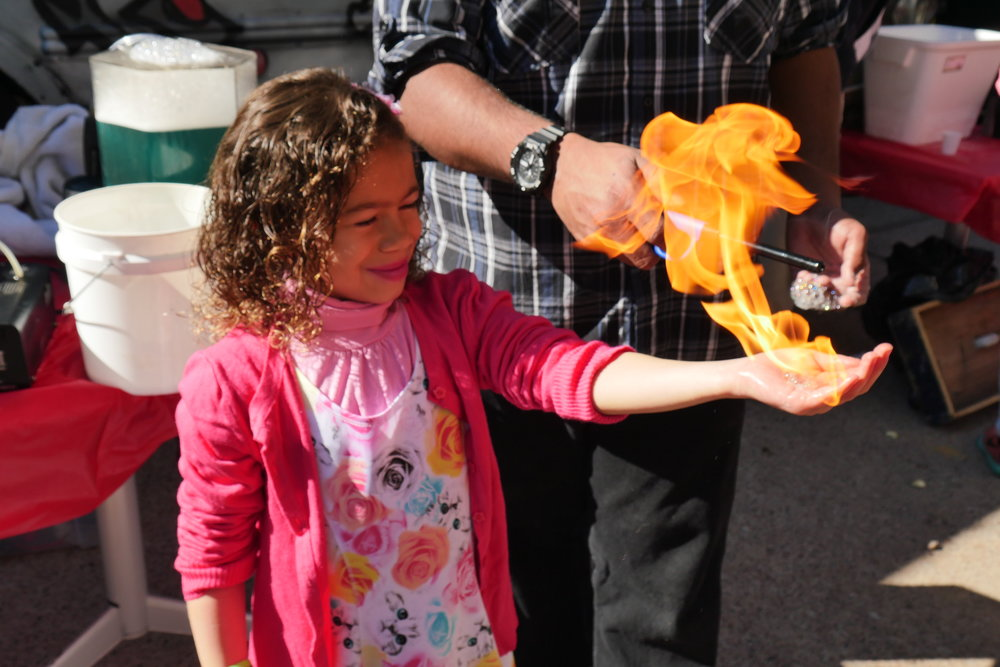 Brisa Mady, 6, briefly holds fire until it dissipates into the air during an outdoor physics demonstration. (Nicholas Serpa/DD)