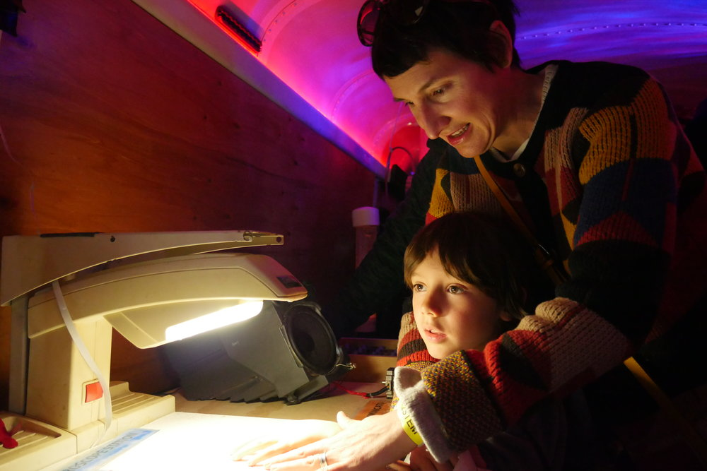 Carrie Wheeler and her son Wilson Wiggins, 5, examine their hands under a microscope inside the Physics Bus exhibit. (Nicholas Serpa/DD)