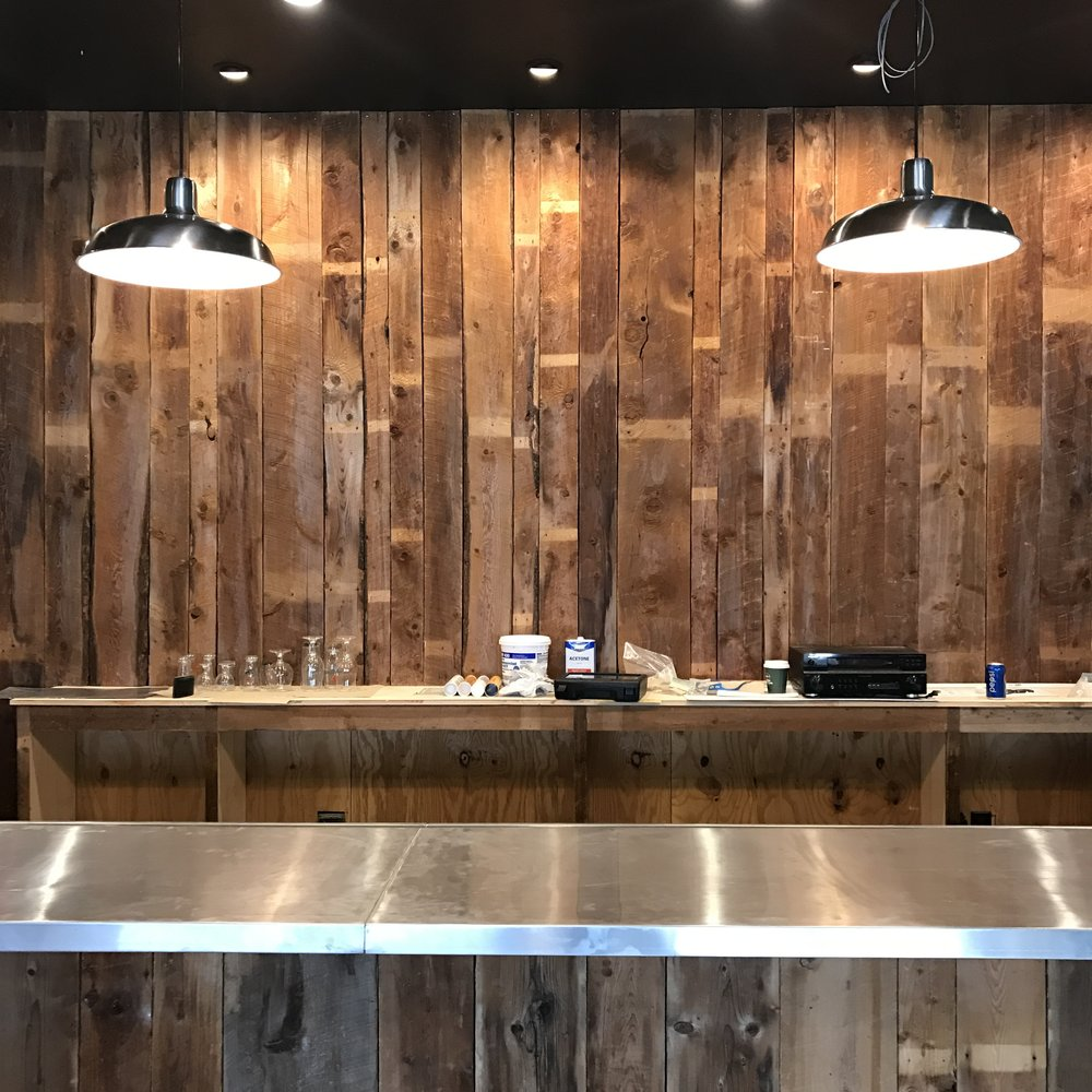 The bar is coming along nicely! Repurposed barn board and zinc top bar.