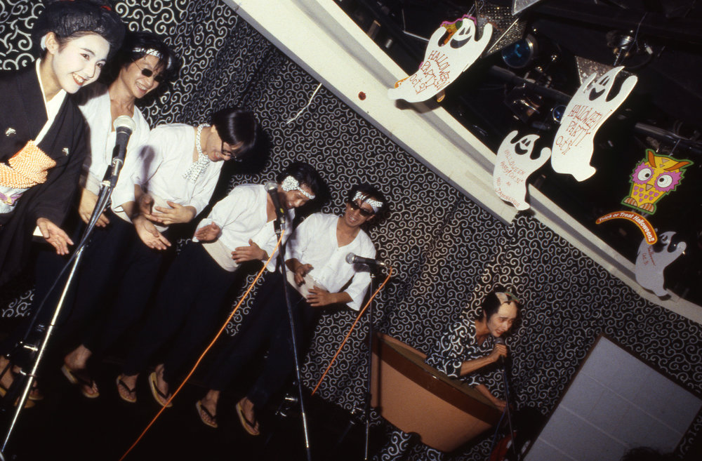 "Numata Genqui performing as the ""Bonsai Kozoh,"" with chorus. Roppongi, Tokyo, ca. 1986"