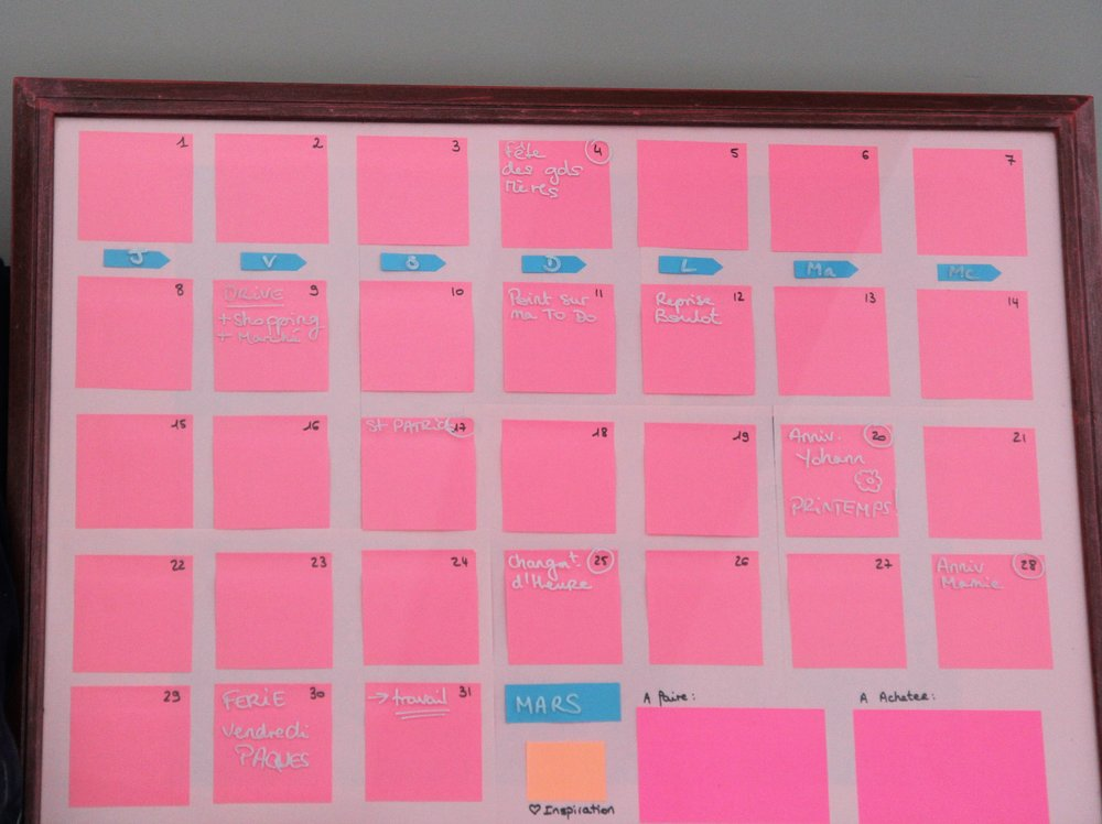 """J'ai récupéré un vieux cadre inutilisé. J'y ai inséré des Post-it numérotés et des papiers de couleur pour figurer les jours, le mois et les """"to do"""". J'utilise un stylo """"craie"""" pour mes annotations (ça marche aussi avec un feutre effaçable pour tableau blanc). Chaque fin de mois, j'efface tout, je n'ai qu'a réinscrire le mois, les jours de la semaine, et mes nouveaux moment forts."""