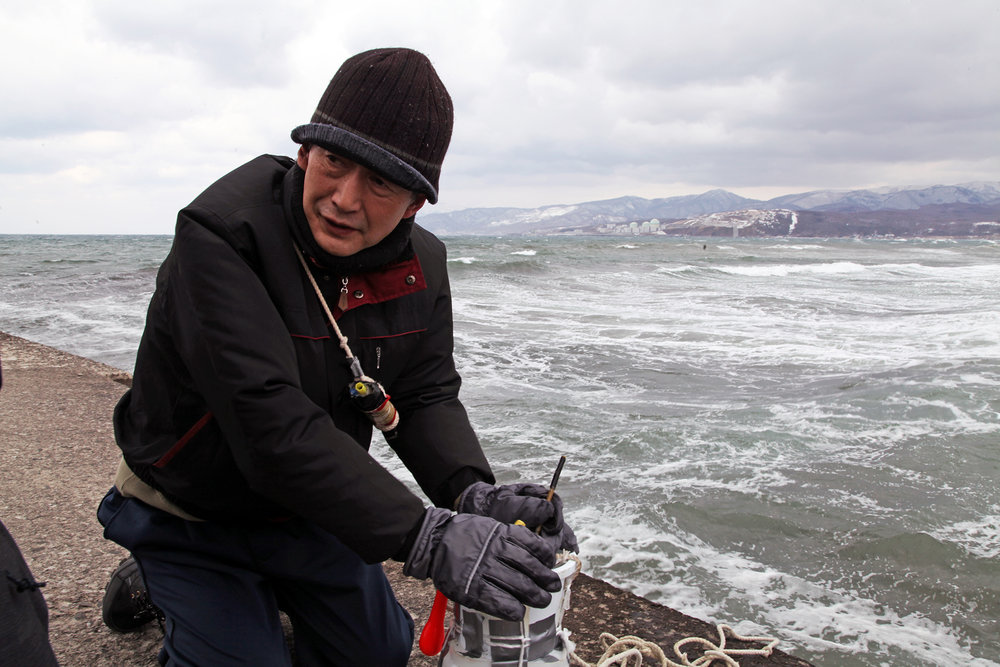 Takeichi Saito taking the temperature of the sea water at Iwanai. Tomari Nuclear Power Station is in the background. Image: authors.