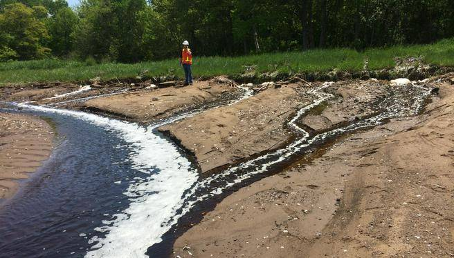 Untreated kraft pulp mill effluent flows from a broken pipe. through a wetland and into Pictou Harbour in 2014.
