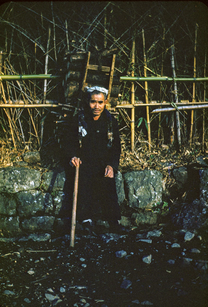 473-Man with Pack in front of Bamboo Fence