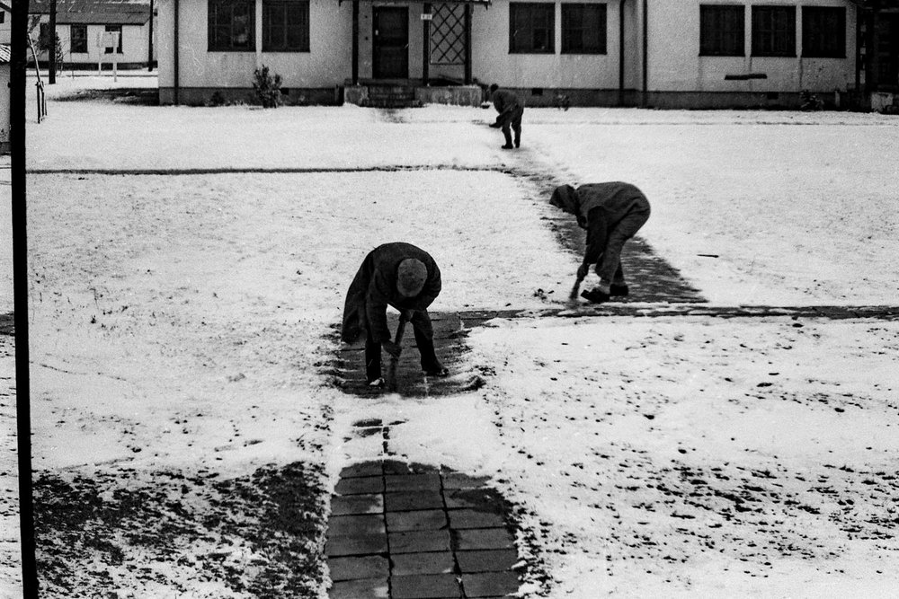 552- Men sweeping snow off of paths