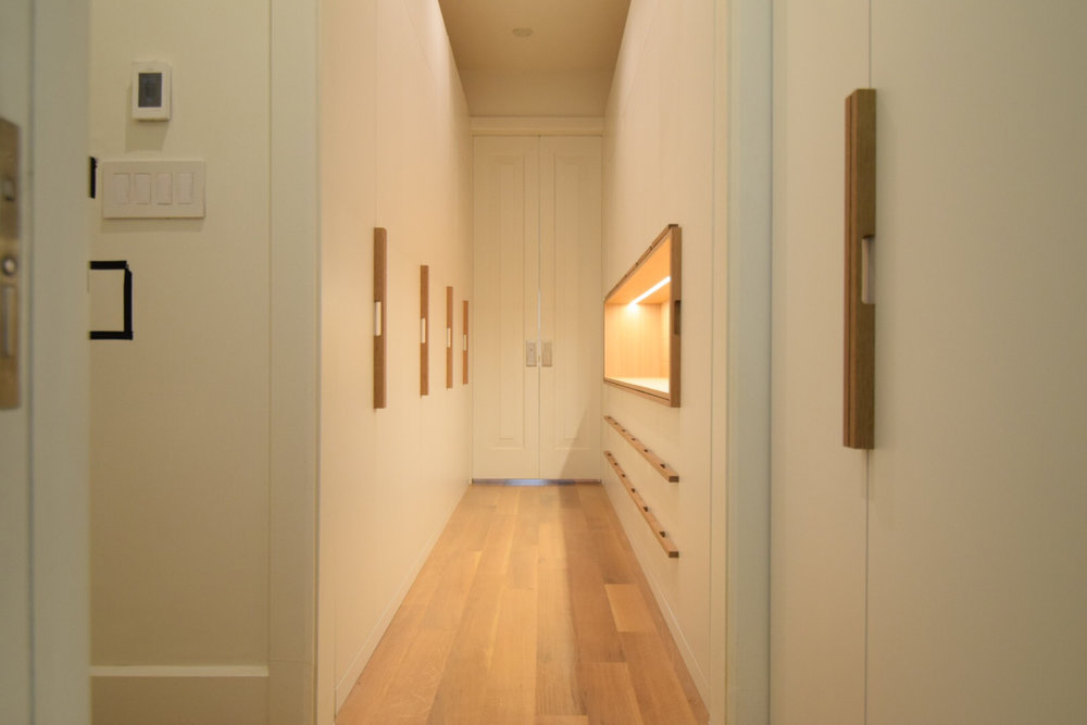 custom-walk-in-closet-white-lacquer-finish-maple-interior-white-oak-handles-white-oak-accent-open-display-cabinet.jpg