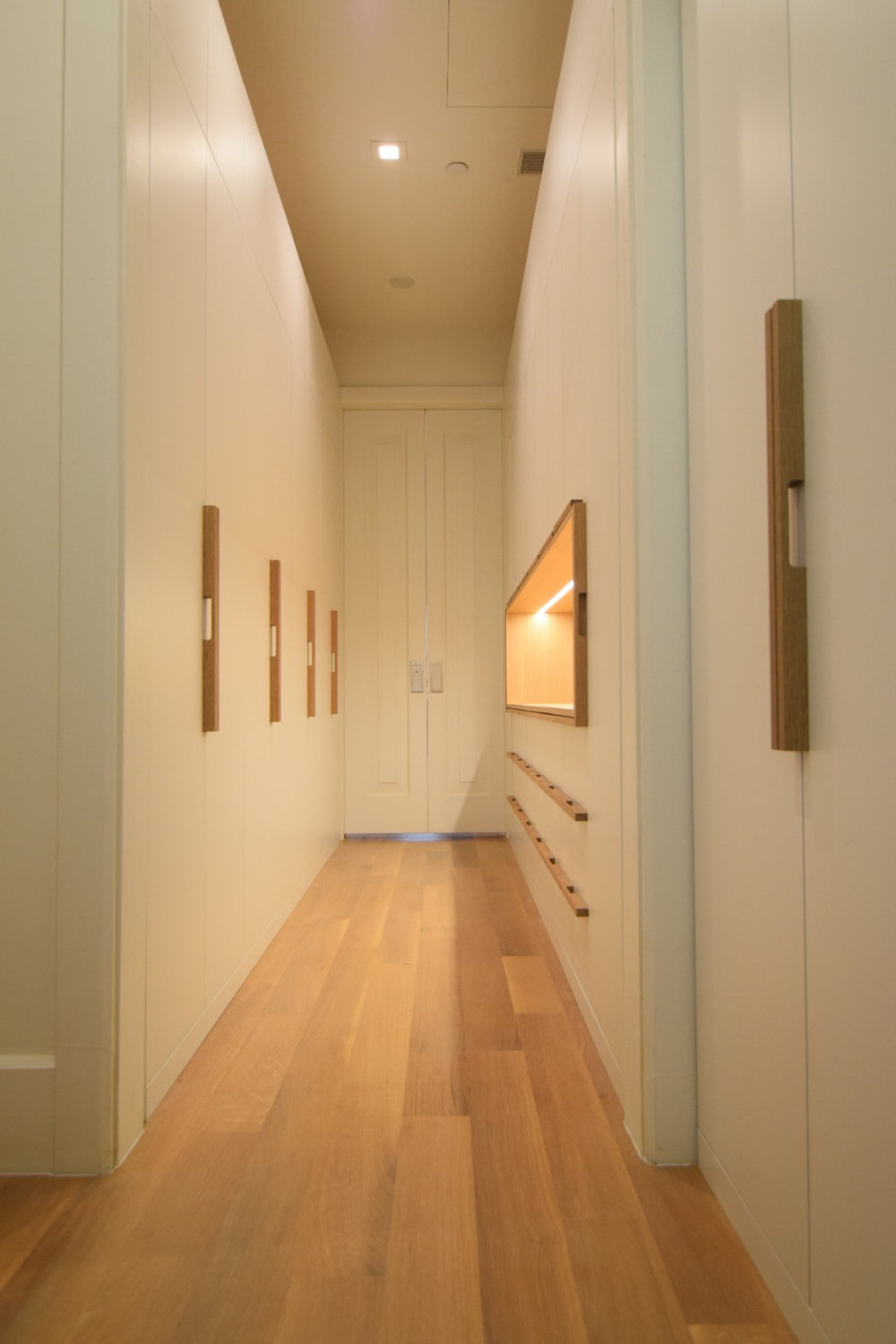 custom-walk-in-closet-white-lacquer-finish-maple-interior-white-oak-handles-white-oak-accent-open-display-cabinet-portrait-view.jpg
