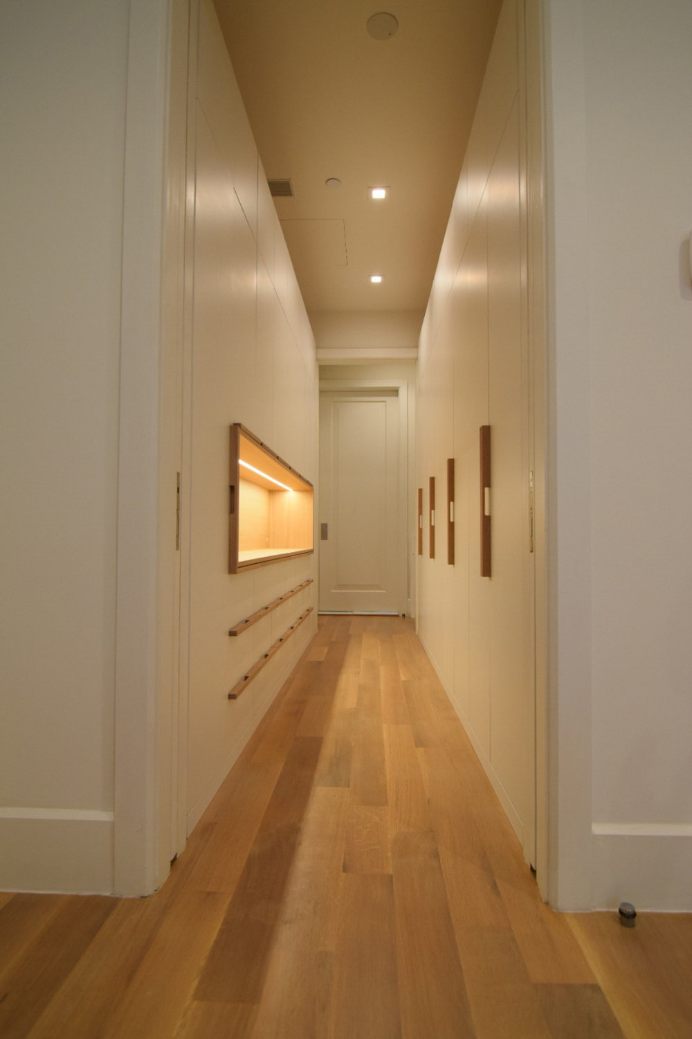 custom-walk-in-closet-with-drawers-and-open-accent-cabinet-white-lacquer-finish-maple-interior-white-oak-handles.jpg