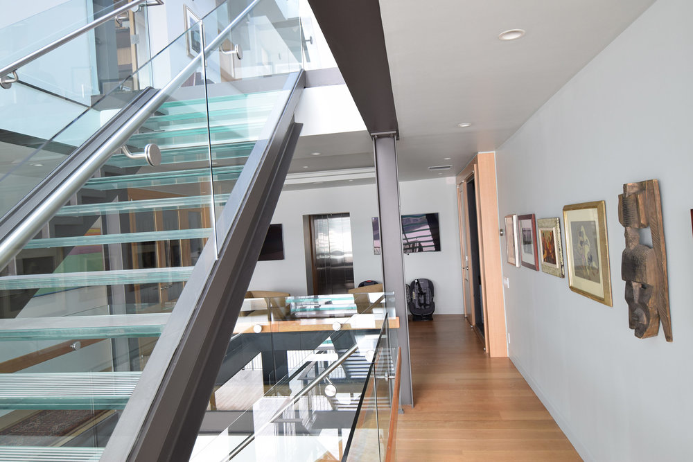 Staircase view to custom Rift Anigre Elevator & two Rift Anigre Wine Closets with Walnut Interiors