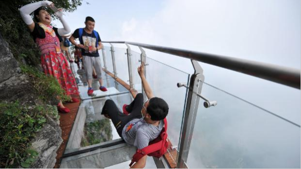 """Tourists on China's """"Coiling Dragon Skywalk"""" – a glass-bottomed path winding around a 300m cliff. If this photo doesn't make you feel weird, you're not as acrophobic as the writer of this article."""