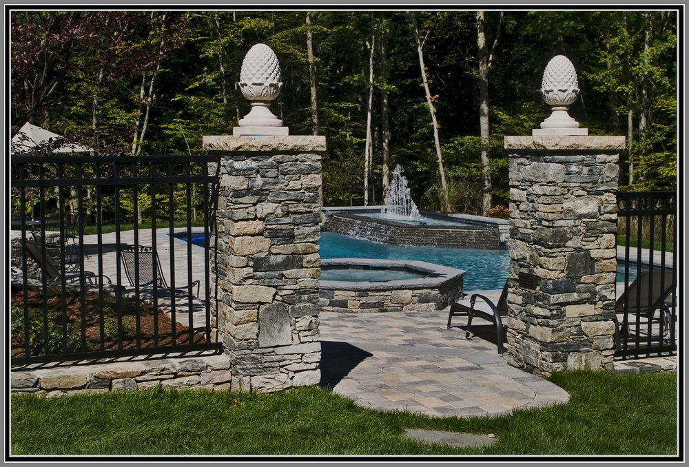 Wrought iron fence and gate with stone columns