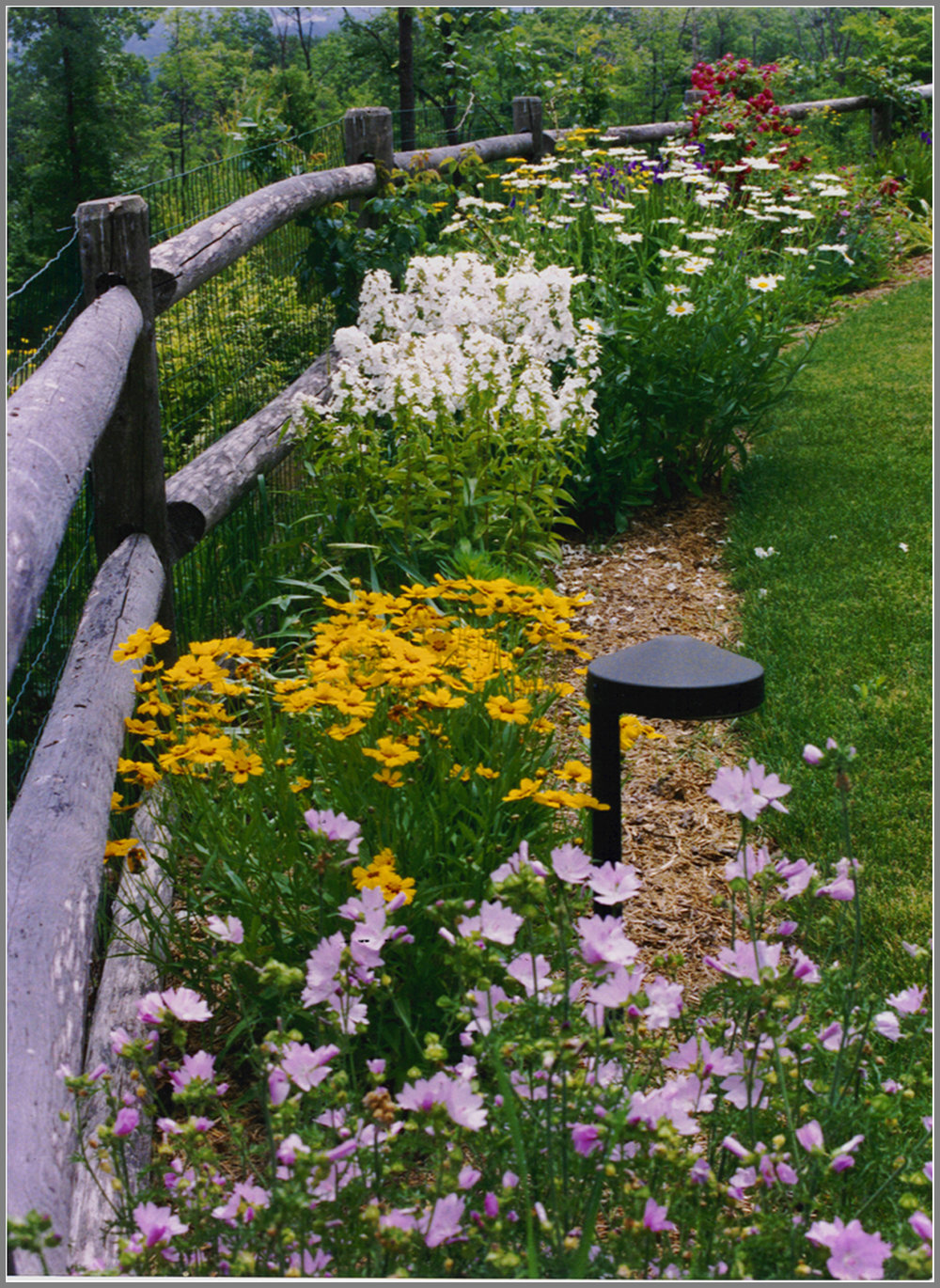 Post and rail fence with gardens