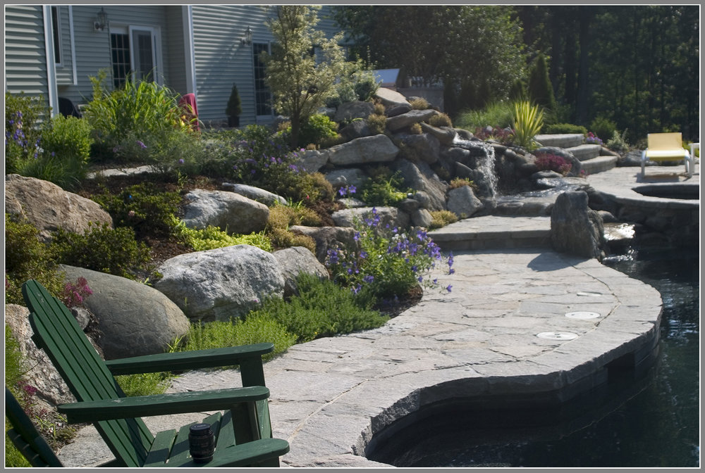 Swimming pool landscape with rock garden and stone decking