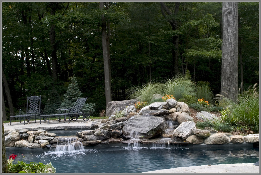 Pool with waterfalls and natural stone spa wall.