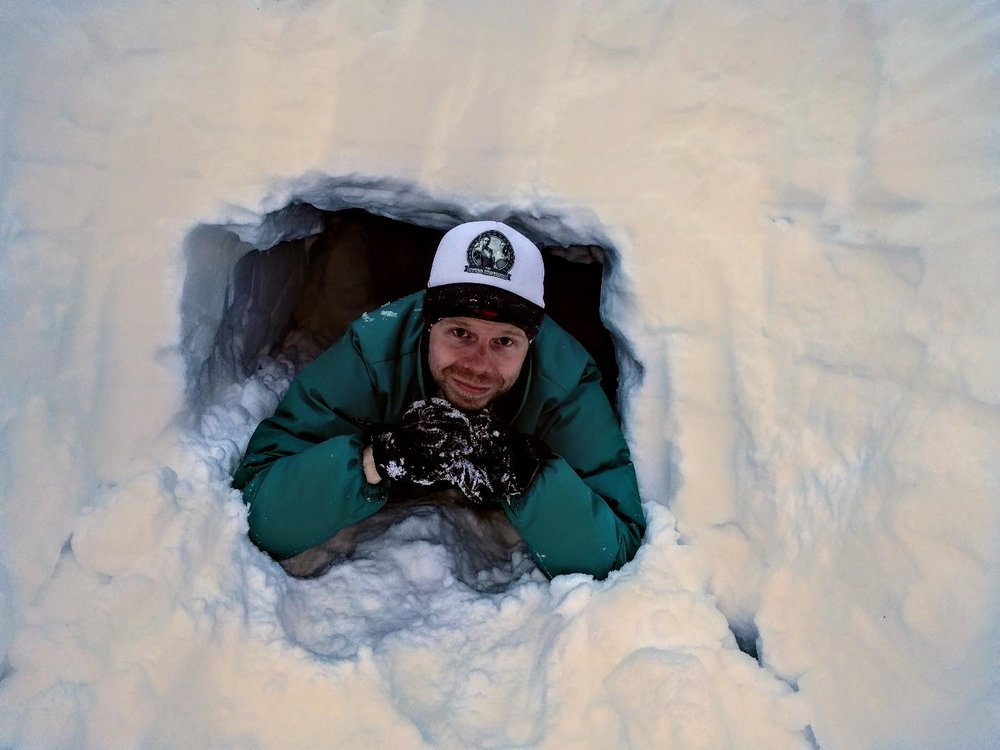 Brian lounges in the quinzhee entrance. It should be noted that he opted to not sleep here for fear his white ball cap would be lost in the white snow. Photo by Brian.