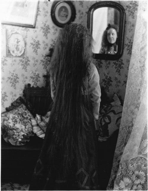 Long-haired woman looking in a mirror, Cornwall. [ca. 1905] / Archives of Ontario / C 150-5-0-0-87 / Marsden Kemp fonds