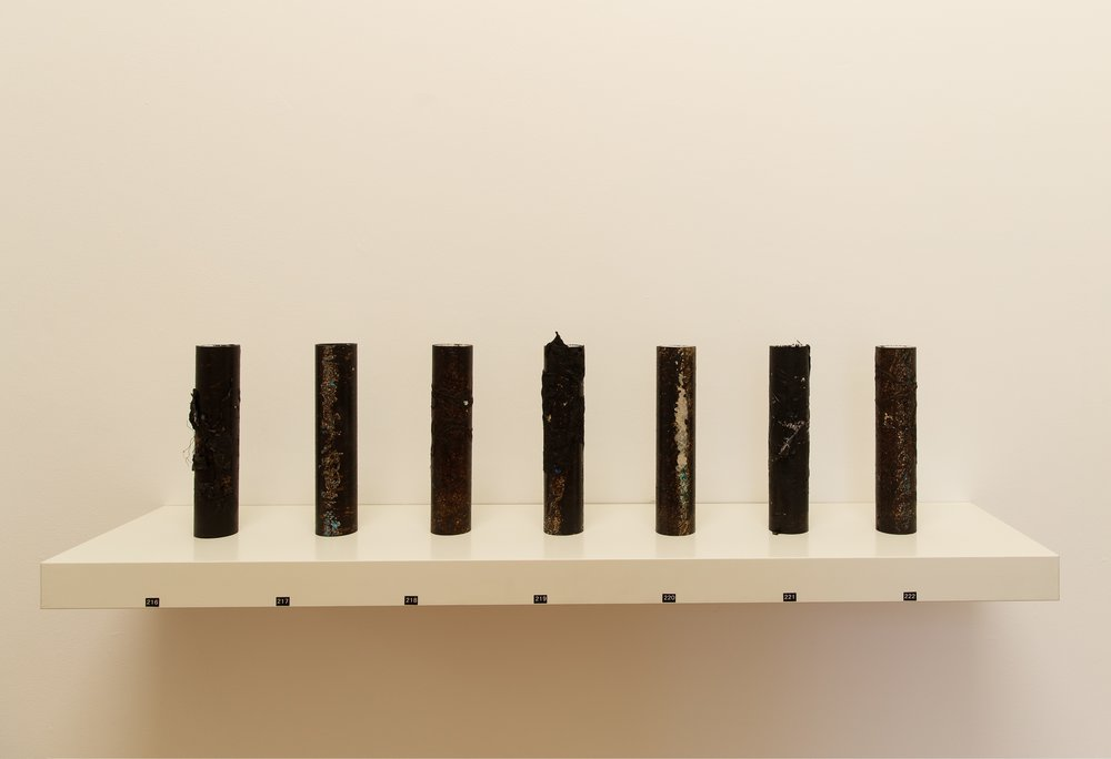 Remains # 1 - 7   bitumen rubber, detritus on PVC pipe  22.5 x 4.8 x 4.8 cm each  Photograph James Field, courtesy Adelaide Central School of Art