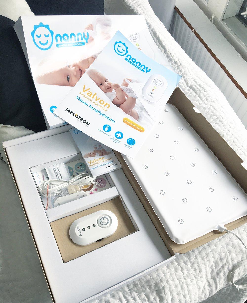 Nanny pakkaus sisältää itse hälyttimen kiinnityshihnalla, sensoripatjan, jatkojohdon sekä suomenkieliset käyttöohjeet ja ensiapuohjeet.