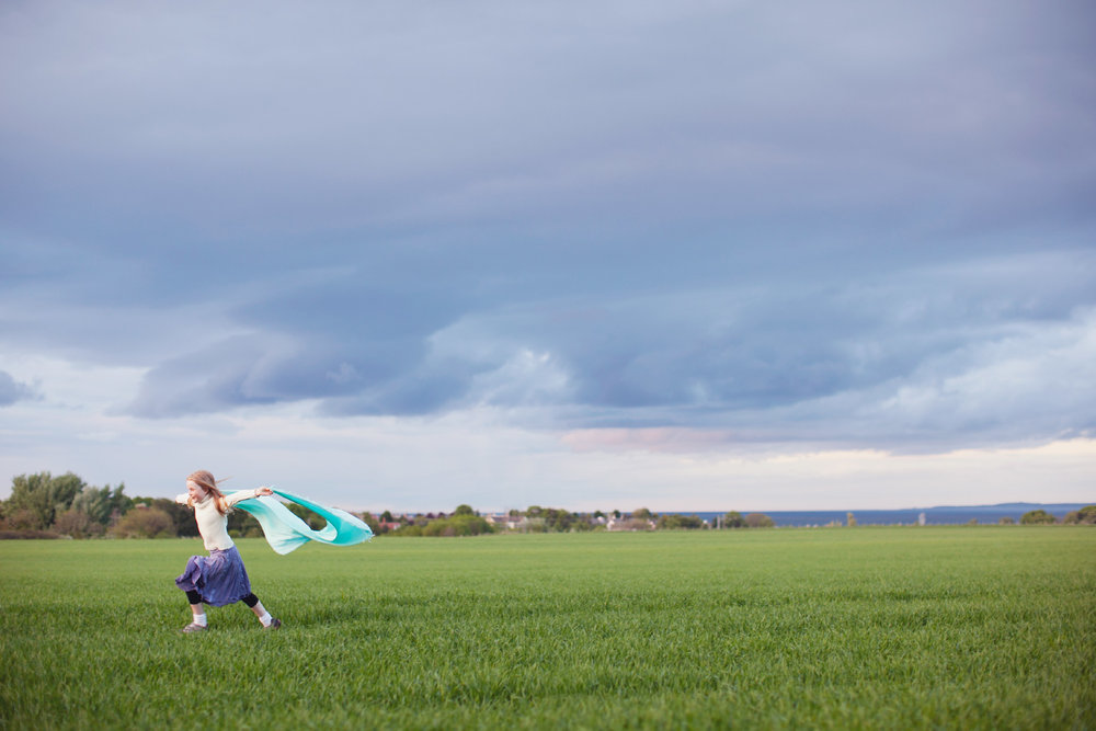 Stacey Van Berkel Photography I Young girl running across a field with a turquoise scarf