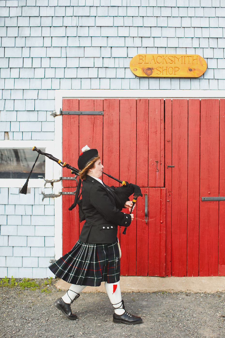 .Stacey Van Berkel Photography I Female bagpiper piping I Grey clapboard barn with red doors I Pictou, Nova Scotia
