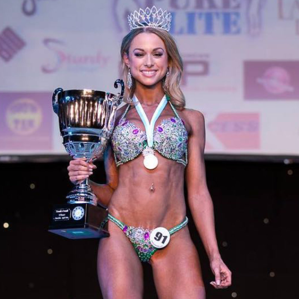 "IMOGEN PARFITT   ""My most recent prep with Adam was for my third fitness show over the course of almost two years working together. After placing second in my last show, Adam gave me the advice to take a year away from competing and to change my focus from getting stage ready to building muscle and making improvements; then when the time was right, start another cut and do another show.  Lots of people said to me ""this is your third show, surely you know what you are doing by now and wont need a coach"" – but I couldn't disagree more. Having Adam as my coach keeps me on track and accountable to someone for all my successes and failures. Adam also has a wealth of knowledge and experience that I believe is totally unrivalled in the industry. His methods and approach to diet and training are based on fact and also your own personal requirements. I am sure that at times Adam knows my body better than I do.   I had a total of 14 weeks prep after a solid 12 months off of strict dieting. Adam provided me with an 'off season' plan which was focused on growing muscle and building the areas that needed most improvement. Over the 14 weeks, Adam gave me weekly feed back and any updates, changes or adjustments were made based on our check ins. I don't live near Adam, so it was all done online and via email. He consistently monitored my progress and we worked together at every step of the way – it doesn't feel like you are left to do it alone. As long as you follow his plan and guidance, you will get the results.  So after taking Adam's advice of a year off, and working with Adam for my most recent prep, I walked away from my competition with First Place in Bikini Tall, Bikini Junior and overall Female of the entire competition. WELL WORTH THE WAIT AND THE WORK.   I wouldn't have been able to do any of this without the help of Adam and I wouldn't trust anyone else with my prep. THANK YOU ADAM!!"""