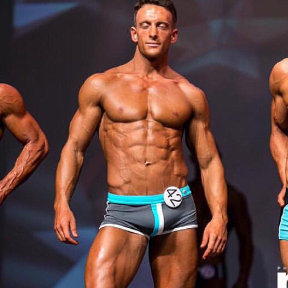 "DAVE FEATHERSTONE   ""I started my training with Adam at the end of June 2015, about a month after singing up for my first competition, Miami Pro in October 2015.   I was hearing so much ""BroScience"" when discussing competing which started to confuse me so I started looking for a coach. I followed Imogen Parfitt on Instagram for a while and saw her transformation whilst being coached by Adam. Adam had also won the competition himself so I knew Adam would be perfect for me.  We live too far apart for one-to-one training so Adam coached me online, at no point was this a problem in the slightest. From Day 1 Adam was on hand with the nutrition program, training and answering any questions I had. Adams responses were always very prompt and clear.  Within a short space of time I noticed change so my motivation was sky high and I knew I could 100% trust the advice Adam was giving me. At times when I struggled to motivate myself I'd get a message off Adam which was the little nudge I needed to keep going.  The result; I won my very first competition taking the Under 75kg Fitness Model title and winning my Pro Card. The transformation pictures speak for themselves. I could not have achieved this without Adam and I'm excited to work on our next project(s).  I can't recommend Adam highly enough for competition prep."""