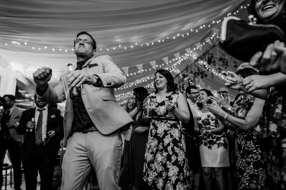 wedding guests dancing authentically photographed in black and white