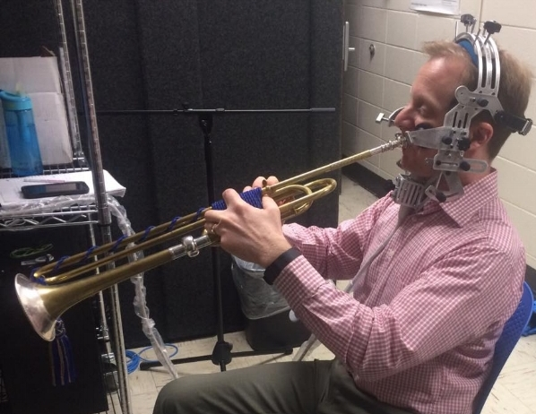 Dr. Jason Dovel  playing baroque trumpet while using ultrasound probe and headset.