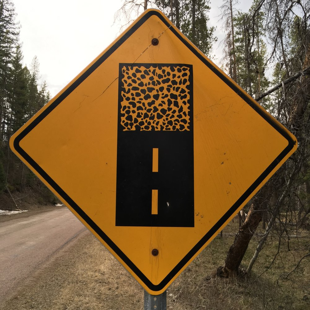 Paved/Gravel road sign.png