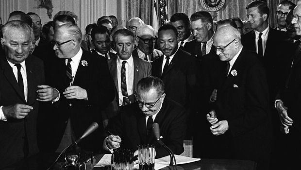 President Lyndon B. Johnson signing the Civil Rights Act of 1964. Martin Luther King is just to his right looking on.