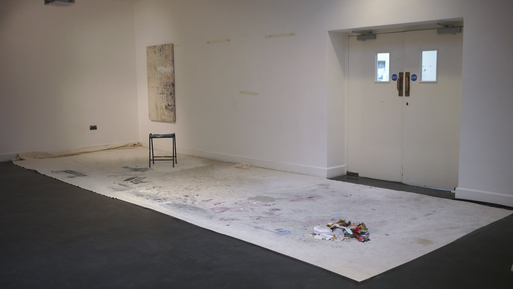 Ally McGinn (2017)  Studio.  Installation test view. Canvas with collected marks, stretchers, masking tape, acrylic paint and chair, size varies  Forcing the viewer to walk on the canvas, by placing it on the floor in a way that doesn't allow any alternative, questions the value of the work, the moment of finishing and the way the viewer sees and interacts with the work.  Each use, or misuse, of canvas invokes a different conversation about the same subject.