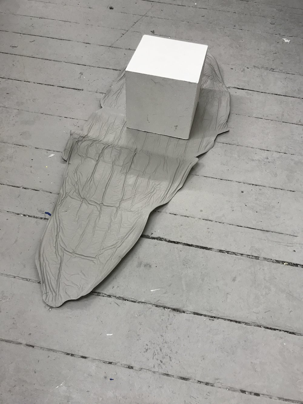 Ally McGinn (2017) [Studio documentation].  The white cube and grey floor. A large paint skin, made on the floorboards, reflecting the shape of the floor in the form. The white cube is a bit of an obvious reference but nonetheless is aesthetically pleasing.
