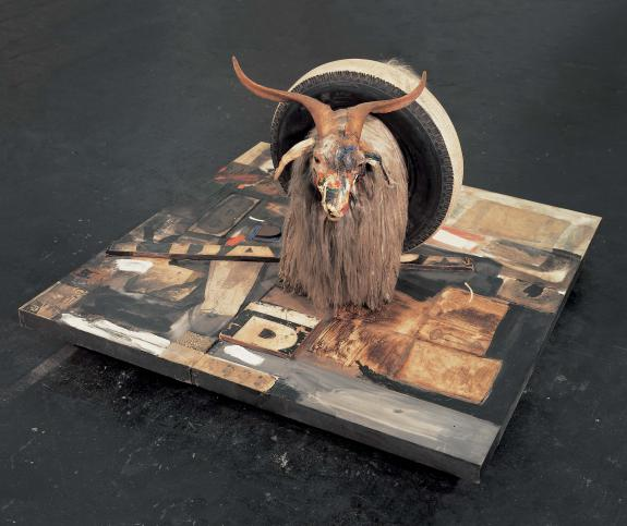 Robert Rauschenberg (1955-59)    Monument . Combine: oil, paper, fabric, printed paper, printed reproductions, metal, wood, rubber shoe heel, and tennis ball on canvas with oil and rubber tire on Angora goat on wood platform mounted on four casters. 106.7 x 160.7 x 163.8 cm.