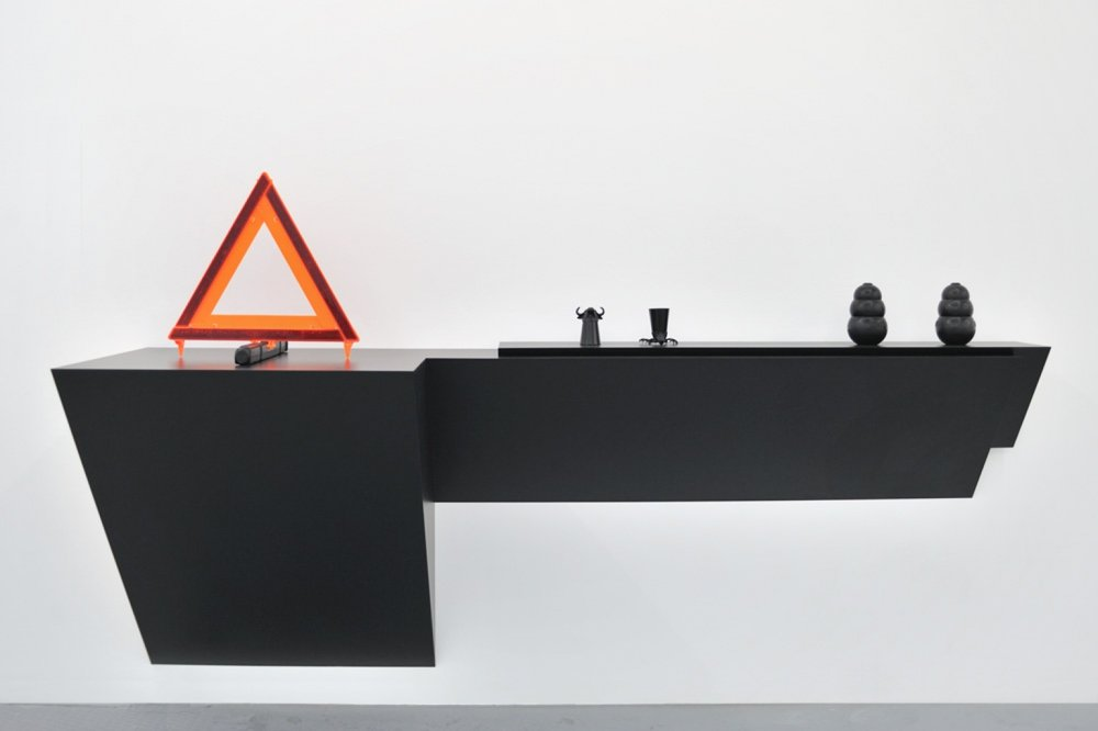 Haim Steinbach (2009)  Untitled (emergency sign, short glasses, dog chews).  Plastic laminated wood shelf, plastic emergency sign, 2 glass and metal shot glasses, 2 rubber dog chews. 125.7 x 222.3 x 68.6.