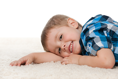 Boy in blue shirt laying on the carpet smiling