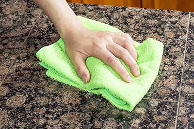 Cleaning Granite Countertop with green cloth