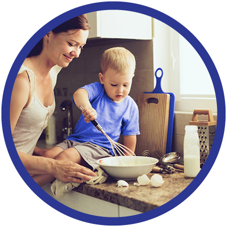 Boy and his mother stirring eggs on granite countertop