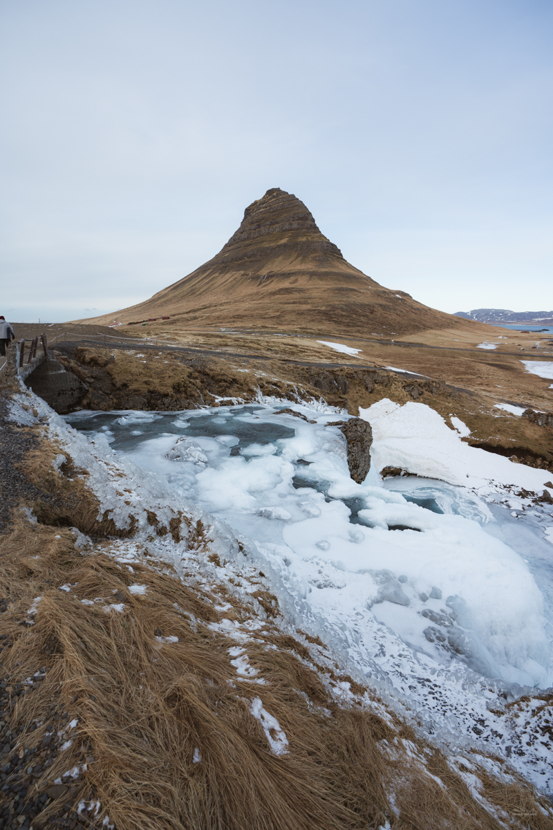 The frozen Kirkjufellfoss and the mountain of Kirkjufell