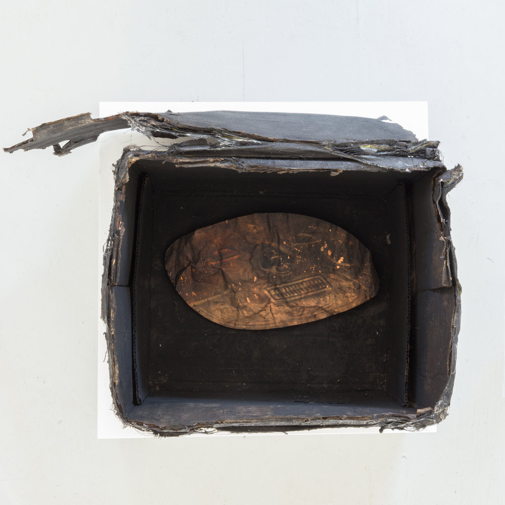 "Harold Mendez. ""Untitled (Death Mask),"" 2015. Burned cardboard box, soot, toner, oxidized copper reproduction of pre-Columbian death mask from the Museo del Oro (Bogota, Colombia). 14"" x 20"" x 14"""