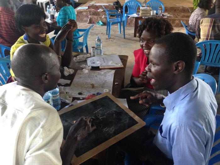 Supervisors and co-ordinators of Speed Schools in Gulu practising the 'Circle and Square' board game during a holiday training session.