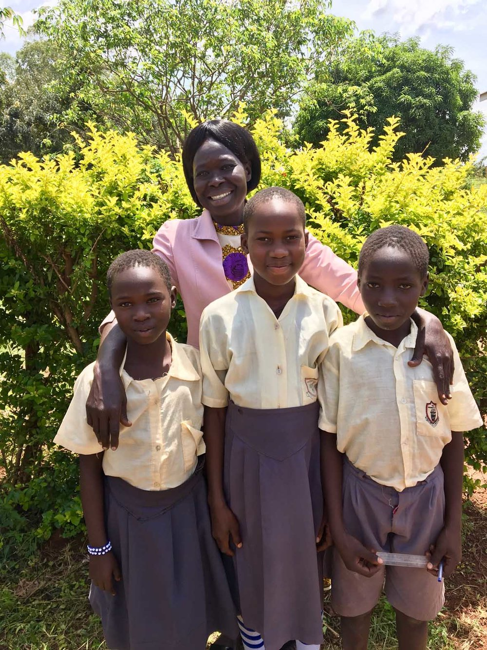 Cubu Primary School P3 teacher with the three best readers in the school after the end of year Early Grade Reading Assessment (EGRA).